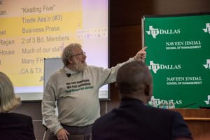 Image: Bill black pointing to a slide while discussing fraud.
