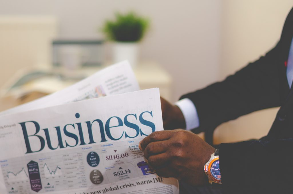 Image: man in suite holding Business section of a newspaper