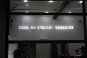 Image: neon storefront sign that reads: Code of ethical behavior""