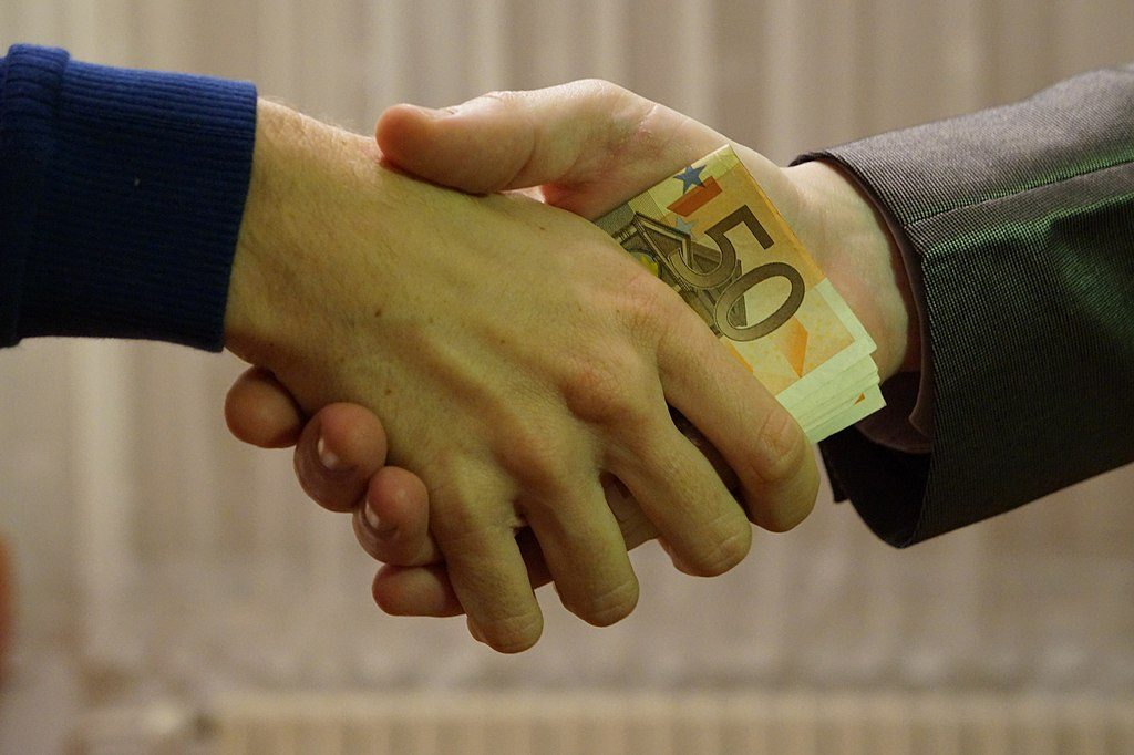 Image: Currency transfer in a handshake