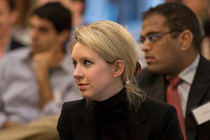 Photo of Elizabeth Holmes listening to a speaker in a crowd.