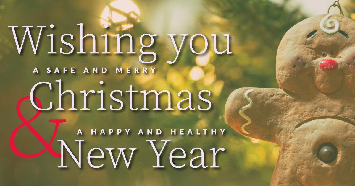 """Image of a gingerbread man ornament hanging on a tree behind the text, """"Wishing you a safe and merry Christmas & a happy and healthy New Year"""""""