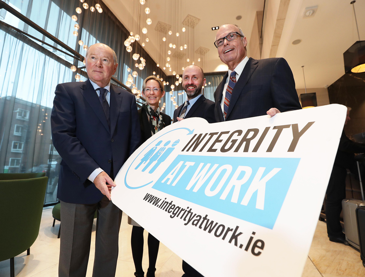 Picture of Justice John Hedigan, Caoimhe de Barra, John Devitt, and Richard Bowen holding an Integrity at Work sign.