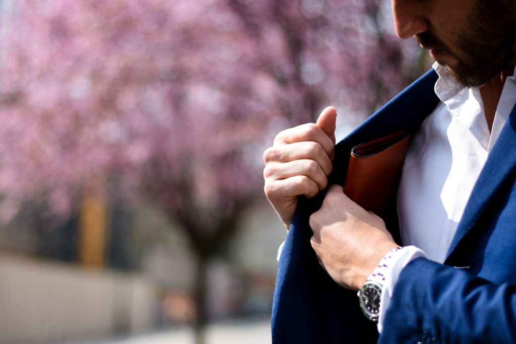 Image: Man putting wallet into his suit jacket.