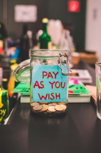 "Image: Open mason jar with coins and ""Pay as you wish"" note inside"