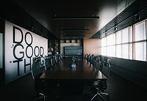 "Picture of empty conference room with ""Do Good Things"" written on the wall."