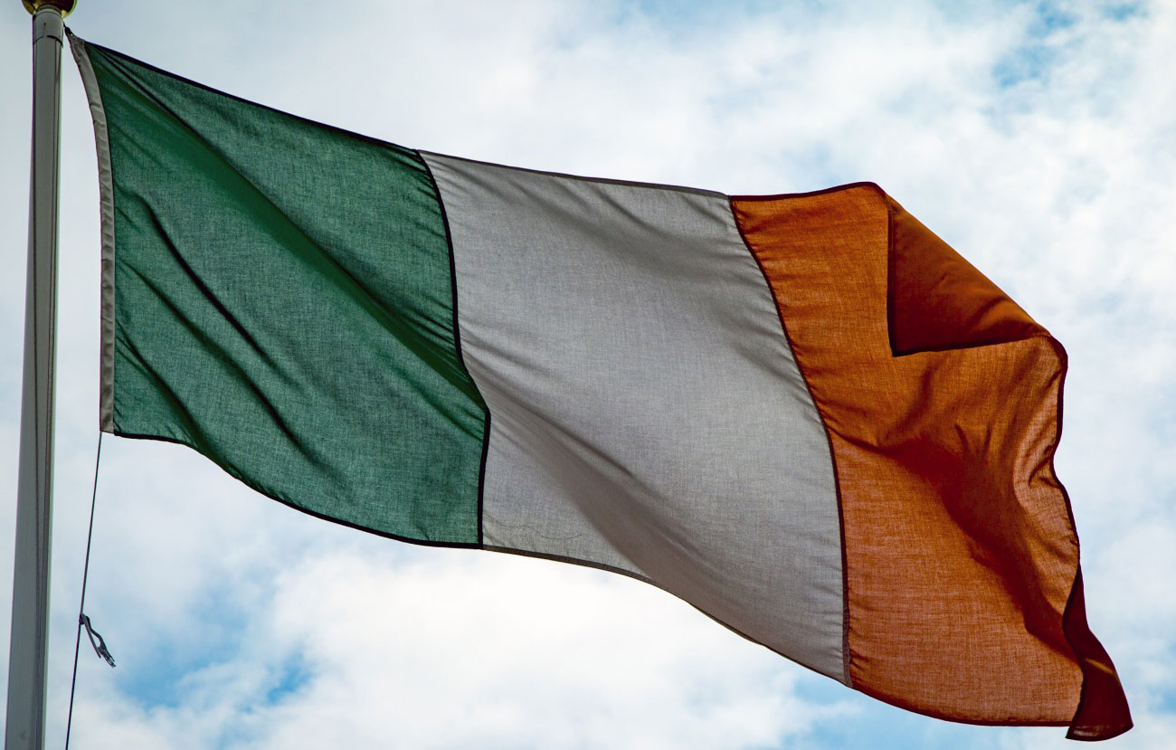 Irish flag against a blue sky with white clouds.