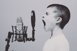 Image: boy singing into microphone with a pop filter