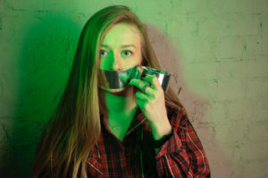 Picture of woman putting duct tape over her own mouth.