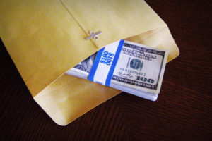 Image: Envelope with stack of $100 bills exposed.