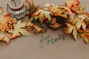 "Fall leaves around a candle wiht ""give thanks"" written on the table"