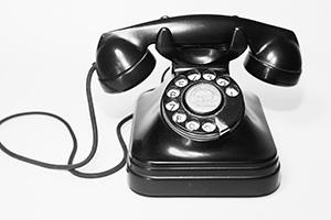 Photo of black rotary telephone.
