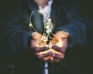 Man holding incandescent bulb.