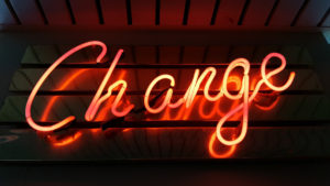 "Image of a neon sign that says ""Change"" in a cursive font."